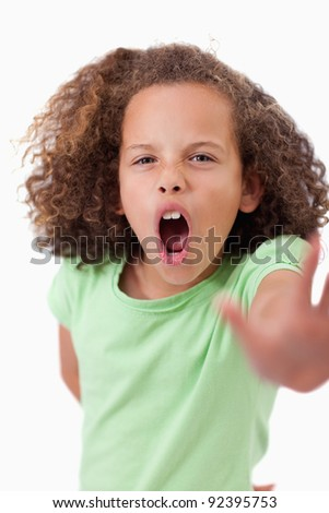 Portrait of an angry girl saying stop with her hand against a white background - stock photo