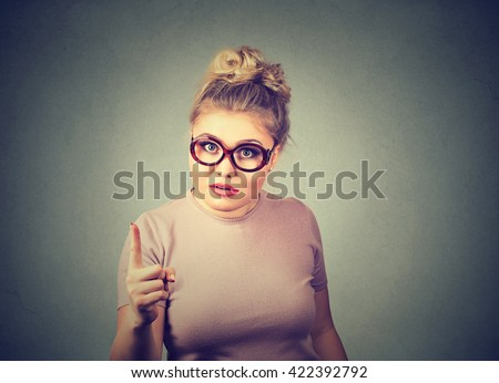 Portrait of an angry woman with finger pointing up looking displeased isolated on gray wall background. Negative human emotion feeling face expression  - stock photo