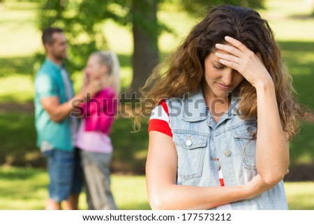 Portrait of an angry woman with man and girlfriend in background at the park - stock photo