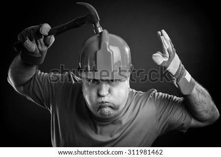 Portrait of an angry worker with protective clothing and hammer. Sepia picture. - stock photo