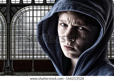 Portrait of an angry young boy - stock photo