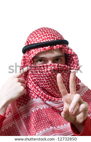Portrait of an arabian young man in traditional headscarf - shemagh. He shows peace sign by hand. - stock photo