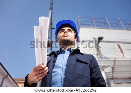 Portrait of an architect holding drawings under his arm - stock photo