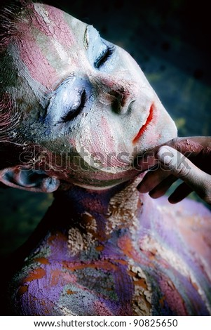 Portrait of an artistic woman painted with clay. Shot in a studio.