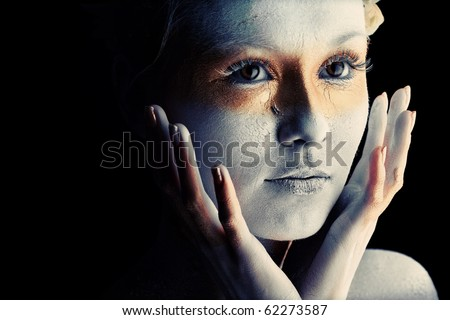 Portrait of an artistic woman painted with white and bronze colors, over black background. Body painting project. - stock photo