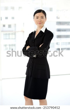 Portrait of an Asian businesswoman standing in a lobby - stock photo
