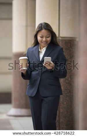 Portrait of an Asian businesswoman standing outside using her smart phone.