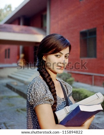 Portrait of an Asian / Indian college student holding books in the campus. - stock photo