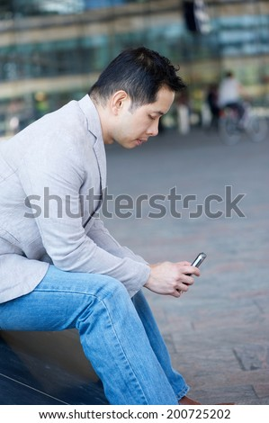 Portrait of an asian man sitting with cellphone outdoors - stock photo