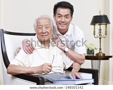 portrait of an asian senior and his adult son. - stock photo