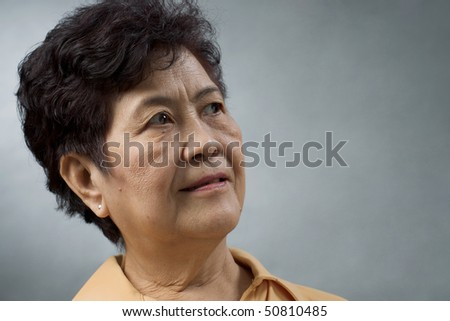 portrait of an asian woman against grey background