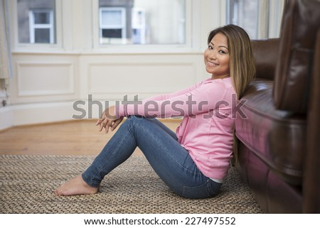 Portrait of an Asian woman sitting on floor, in her living room at home. Looking at camera  - stock photo