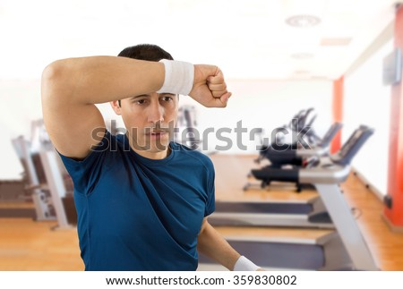 portrait of an athlete standing and wiping sweat after making exercise at the gym
