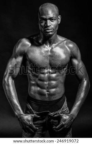 Portrait of an athletic black man on black background. Black and white - stock photo