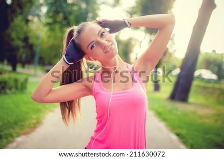 portrait of an athletic girl working out and stretching in park while listening to music, fitness concept - stock photo