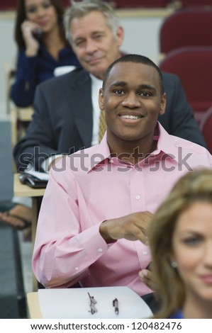 Portrait of an attentive male executive in business lecture amid colleagues - stock photo