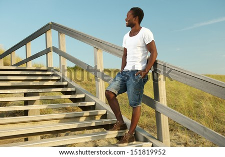 Portrait of an attractive african american male smiling outdoors - stock photo