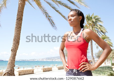 Portrait of an attractive african american sport woman after doing sport in a coastal city by the beach,  proudly standing against a blue sky. - stock photo
