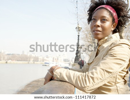 Portrait of an attractive african american woman sightseeing in London's river Thames while on vacation. - stock photo