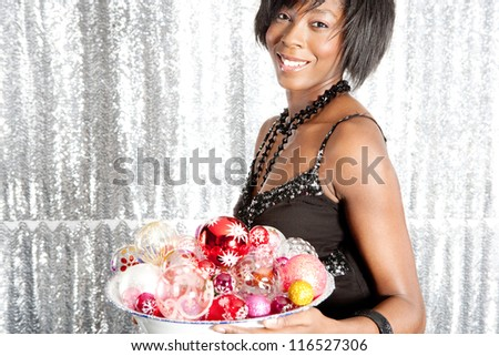 Portrait of an attractive black woman holding a dish full of christmas bar balls against a silver sequins background. - stock photo