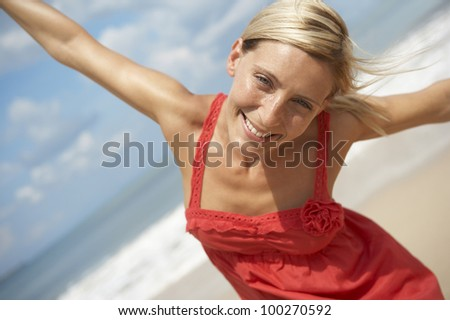 Portrait of an attractive blonde woman on a beach with arms outstretched, smiling to the camera. - stock photo