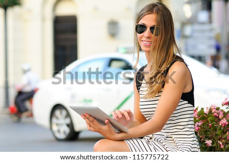 Portrait of an attractive blonde woman with tablet computer in urban background - stock photo