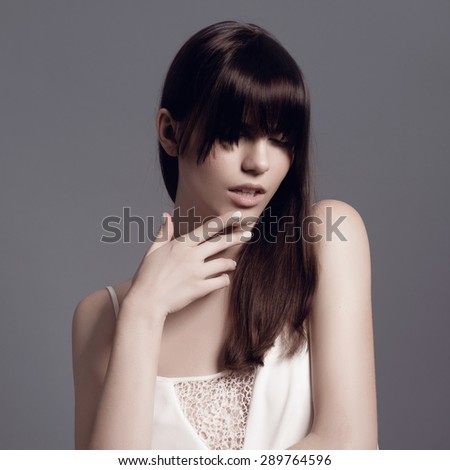 Portrait of an attractive brunette woman in the studio wearing a white dress on a dark background, concept of beauty and health - stock photo