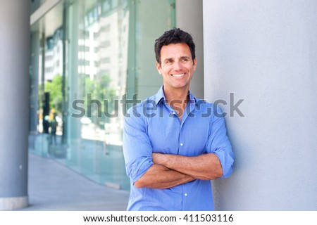 Portrait of an attractive business man smiling with arms crossed in the city - stock photo
