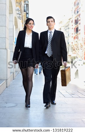 Portrait of an attractive business people walking on the street. Couple working. - stock photo