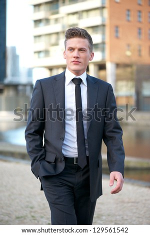 Portrait of an attractive businessman walking outdoors - stock photo