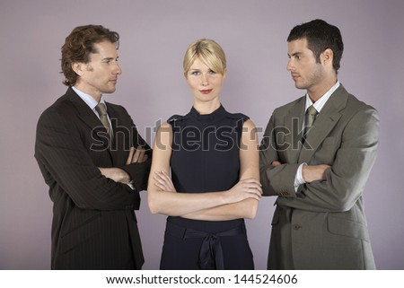 Portrait of an attractive businesswoman surrounded by two businessmen - stock photo