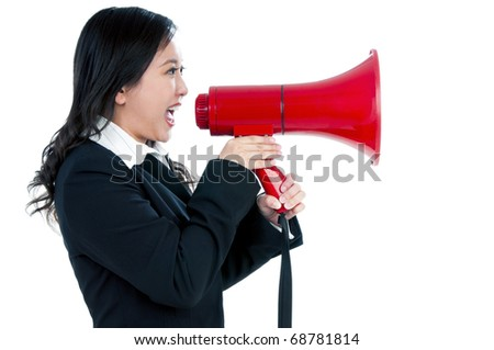 Portrait of an attractive businesswoman using a megaphone over white background.