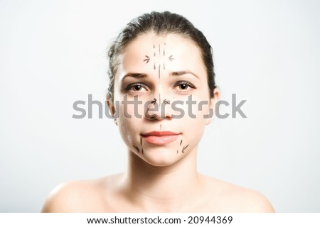 Portrait of an attractive Caucasian lady whose face is marked with lines for facial cosmetic surgery - stock photo