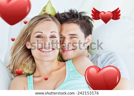Portrait of an attractive couple hugging and relaxing on the sofa against hearts
