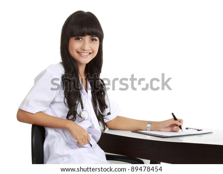 Portrait of an attractive female doctor standing against white background. close up - stock photo