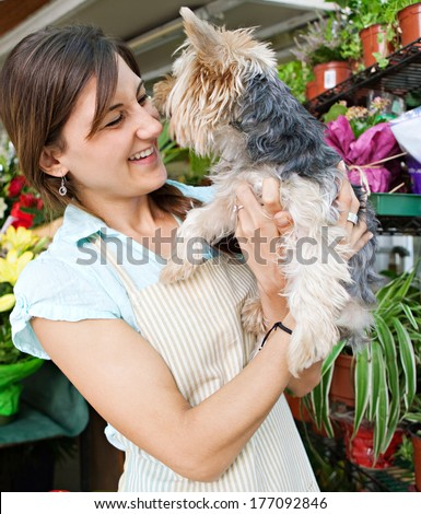 Portrait of an attractive florist kiosk business owner standing in her flower market stall shop, holding her dog pet kissing and laughing during a sunny day. Running a small business. - stock photo