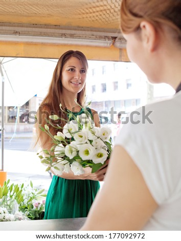 Portrait of an attractive florist store customer client woman buying a bouquet of fresh flowers and smiling at the store assistant in a flower market stall store. Outdoors business shopping.