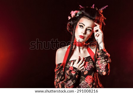 Portrait of an attractive geisha with bright makeup and hairdo. The concept of Asian beauty. - stock photo