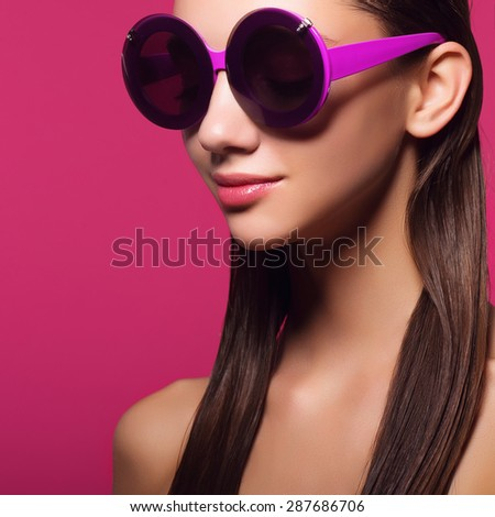 Portrait of an attractive girl in round glasses on a pink background in studio - stock photo