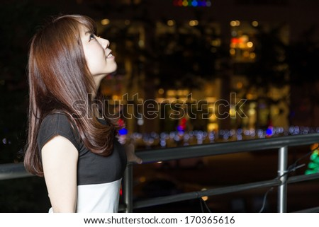 Portrait of an attractive Japanese tourist woman smiling and visiting a shopping mall in the city of Taipei  lights in the background. - stock photo