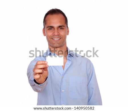 Portrait of an attractive latin man looking at you while is holding a white card with copyspace against white background