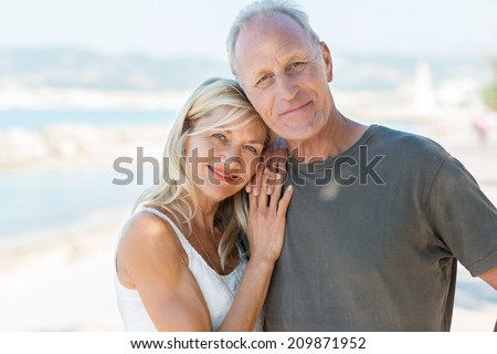 Portrait of an attractive loving middle-aged couple posing close together at the beach smiling at the camera - stock photo