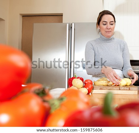 Portrait of an attractive mature woman peeling potatoes in the kitchen at home while cooking healthy organic vegetables, focused and enjoying preparing food indoors. - stock photo