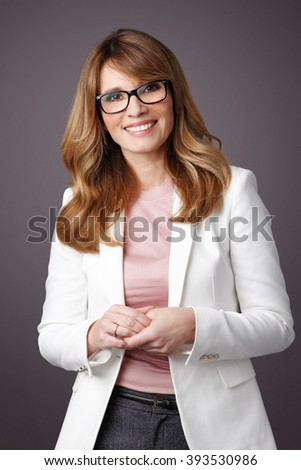 Portrait of an attractive middle age businesswoman standing at isolated background.