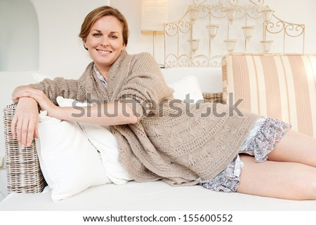 Portrait of an attractive middle aged woman laying and relaxing on a white sofa in a neutral living room at home, smiling at the camera and being serene, interior. - stock photo