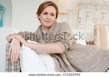 Portrait of an attractive middle aged woman laying down and relaxing on a white sofa in a neutral living room at home, being thoughtful, interior. - stock photo