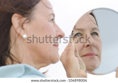 Portrait of an attractive middle aged woman looking into a mirror, with focus set on the mirror image.