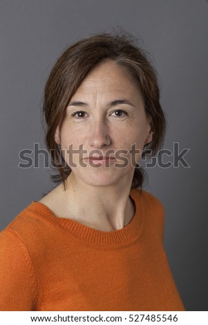 portrait of an attractive middle aged woman posing with self-confidence and wellbeing with a natural relaxed smile over grey background