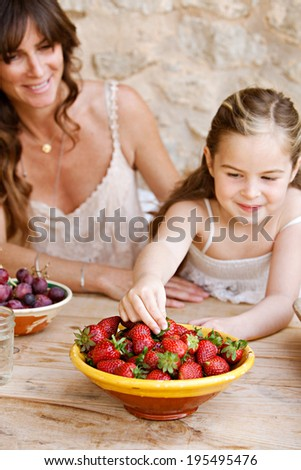 Portrait of an attractive mother and her young daughter eating fresh fruit in a holiday home outdoors, with the girl reaching to pick a strawberry from the wood table. Healthy family lifestyle living. - stock photo