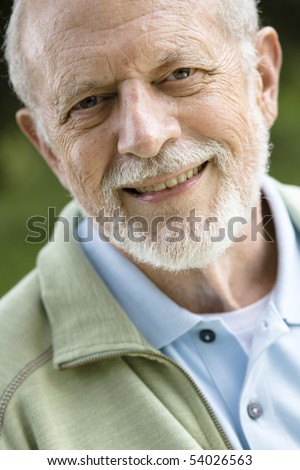 Portrait of an Attractive Old Man With a Beard Smiling Directly to the Camera - stock photo